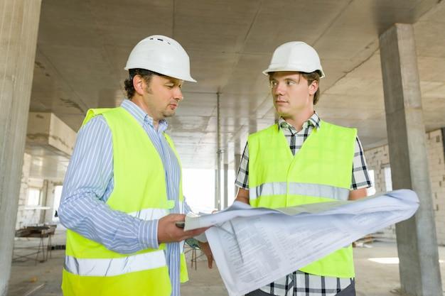 男性の建設労働者と建設現場のエンジニア
