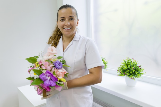 花の花束を持つ女性看護師
