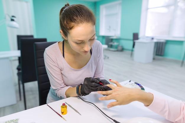 Уход за ногтями и руками в салоне красоты. молодая женщина делает профессиональный маникюр
