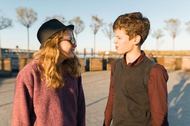 若い男の子と女の子がお互いを見てのカップルの屋外のポートレート