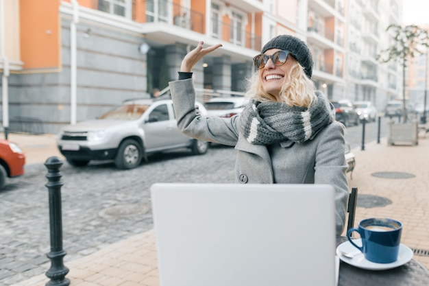 コンピューターのラップトップで屋外カフェで暖かい服帽子の若い女性ブロガーフリーランサー