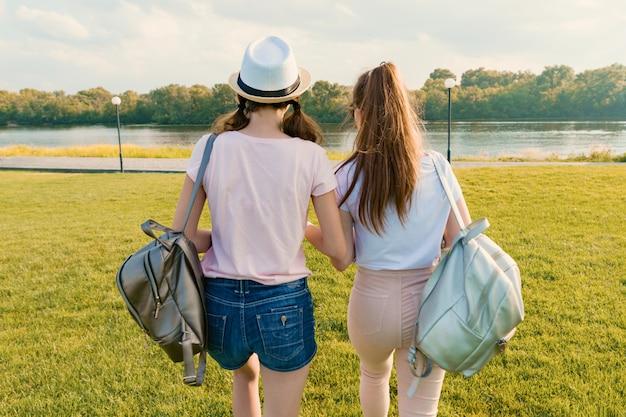 Вид сзади, подруги гуляют в парке на природе