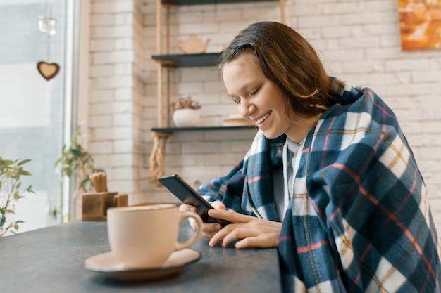 Осенний зимний портрет улыбающейся девочки-подростка с мобильным телефоном в кафе