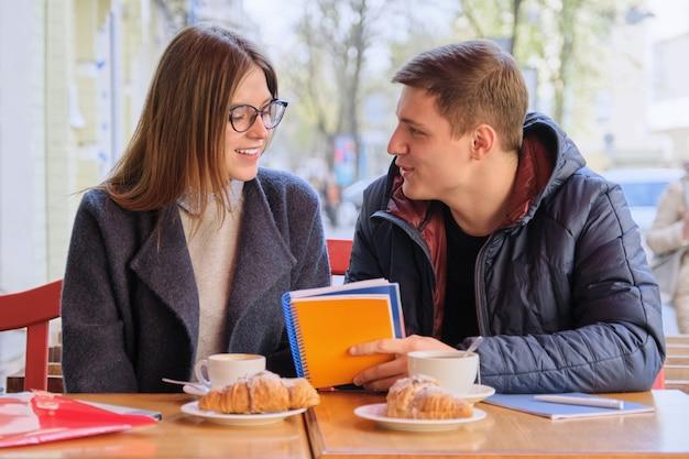 Молодая пара студентов учится в кафе на открытом воздухе