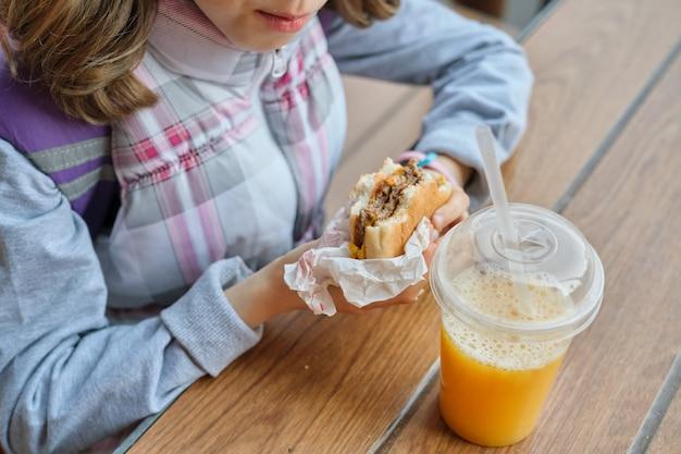 Крупным планом руки ребенка есть гамбургер и пить апельсиновый сок
