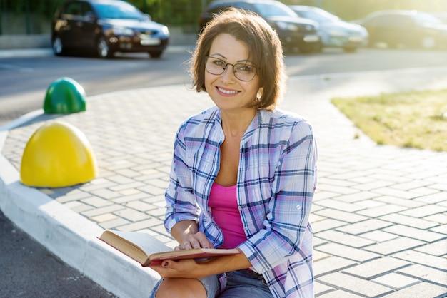 Внешний портрет взрослой красивой женщины читая книгу