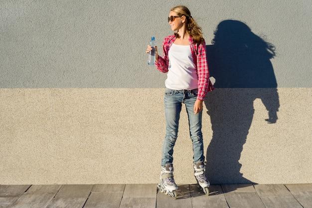 ローラーで履いた水のボトルを持つ少女