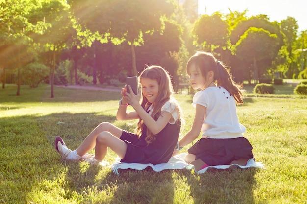 陽気な小さなガールフレンドは、スマートフォンで遊ぶ