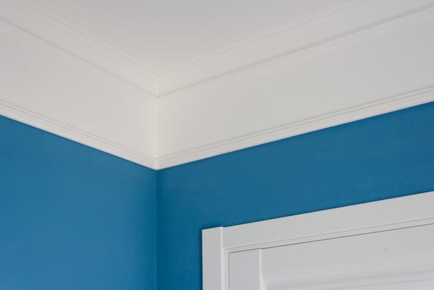 内部の詳細。天井モールディング、青い塗装壁、白いドア