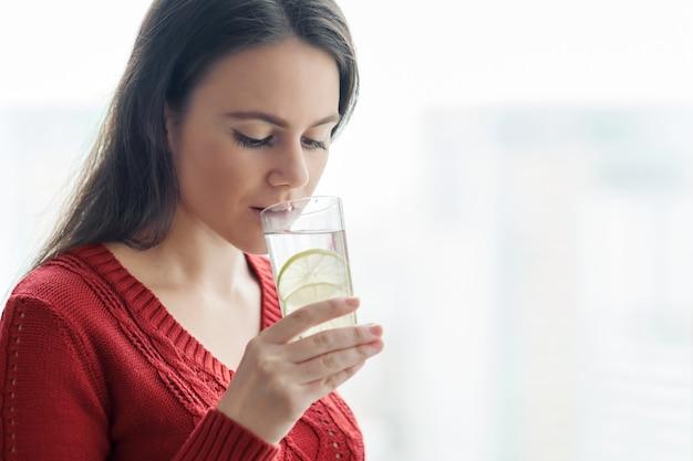 ライムと水のガラスと赤いセーターの女性