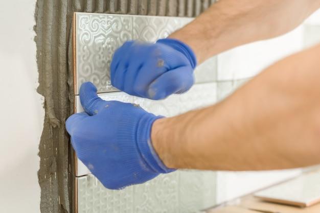 キッチンの壁にセラミックタイルを敷設瓦職人の手のクローズアップ