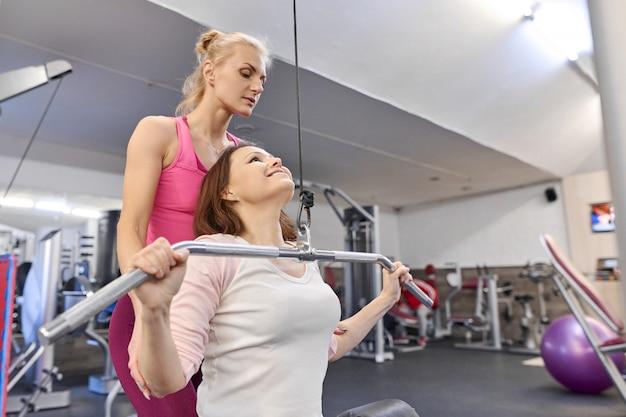 Личный инструктор по фитнесу, помогая летней женщине заниматься в оздоровительном клубе