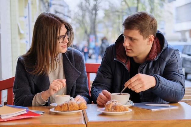 Молодые студенты мужского и женского пола друзей, сидя в кафе на открытом воздухе