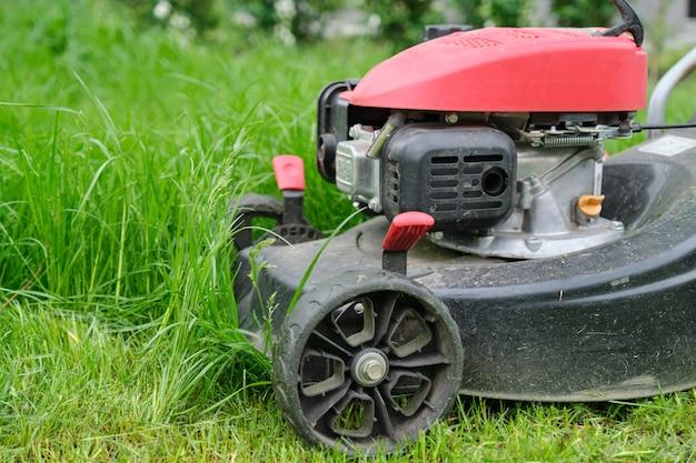 緑の草を刈る芝刈り機のクローズアップ