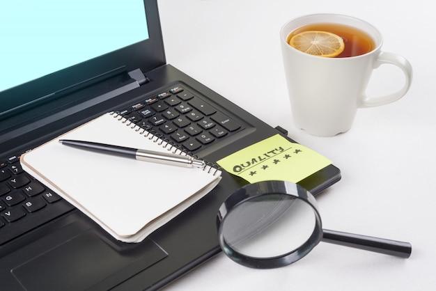 仕事机の上のノートパソコン、単語品質のステッカー