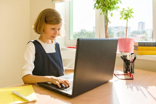 小さな女子高生はコンピューターのラップトップを使用します
