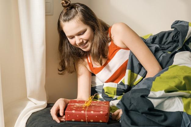 Девочка-подросток смотрит и открывает подарок-сюрприз в коробке