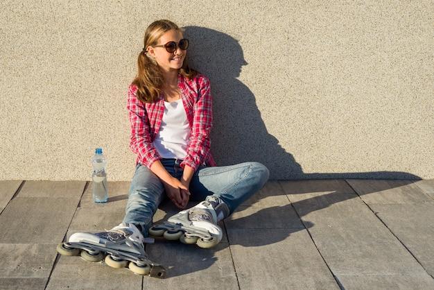 若い笑顔のクールな女の子がローラーブレードで撃つ