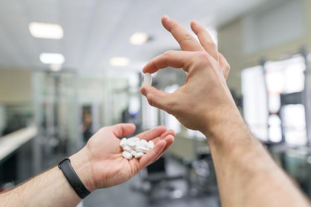 Мускулистый мужчина руки, показывая спортивные и фитнес-добавки