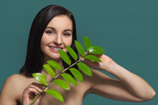 緑の葉と自然の美しさとメイクなしの女性