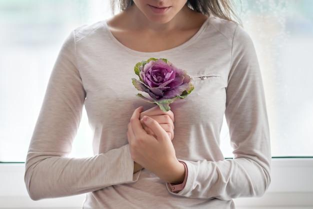 Молодая красивая женщина с фиолетовым цветочным цветком капусты