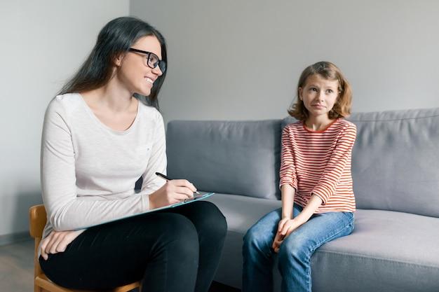Молодой женский психолог разговаривая с терпеливой девушкой ребенка