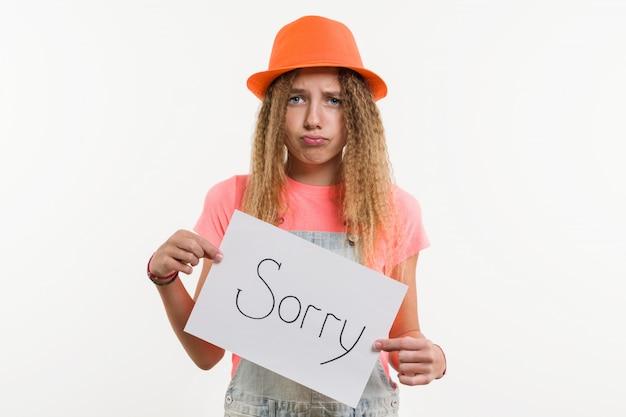 申し訳ありませんがメッセージと看板を持っているかわいい十代の少女キャラクター