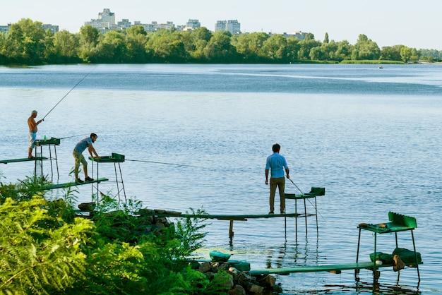 Отдых в городе. мужчины ловят рыбу на реке.