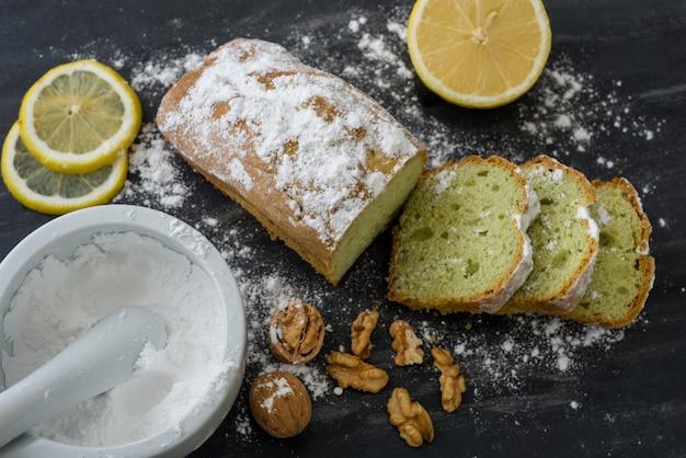 Мятный торт на черной поверхности с лимоном, орехами, сахарной пудрой