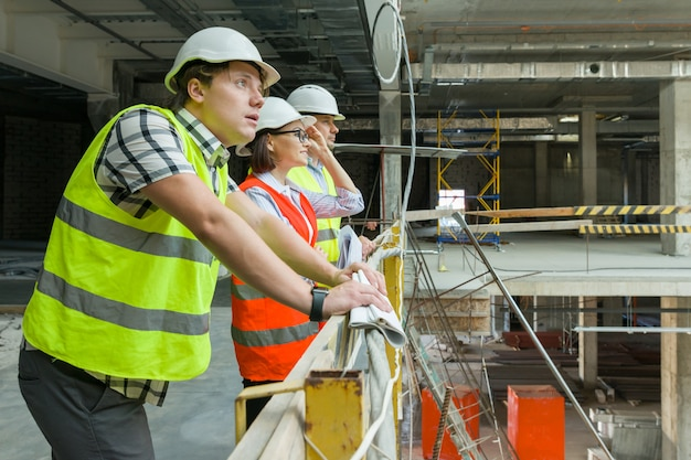 Группа инженеров, строителей и архитекторов на строительной площадке