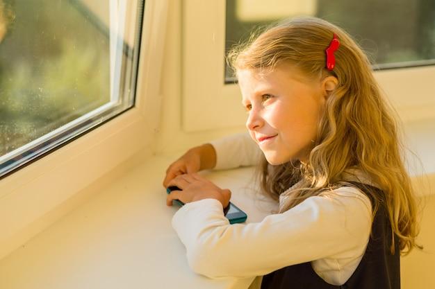 窓の外を見て美しいかわいい女の子