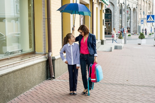 傘の下で学校に一緒に歩いている娘を持つ女性。