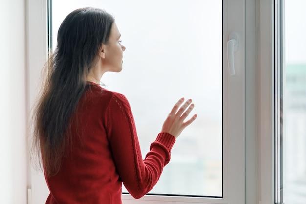 窓の外を見て赤いセーターの若い女性