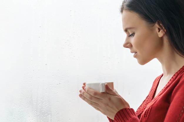 Портрет молодой красивой женщины в кофе красного свитера выпивая.