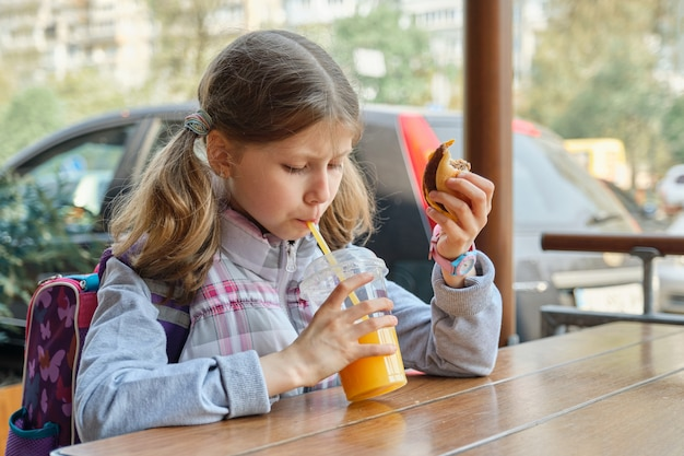 バックパック、ハンバーガーを食べて、オレンジジュースを飲む少女の肖像画