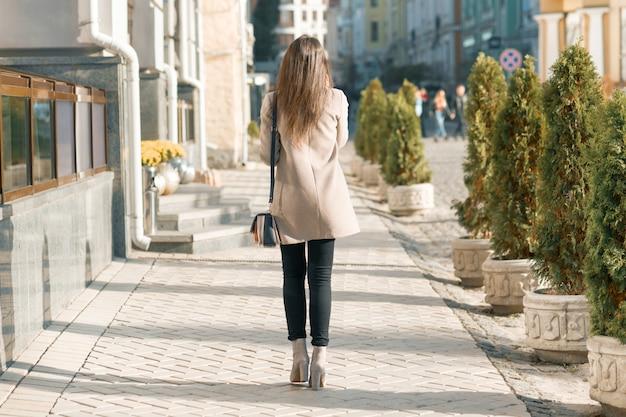 Вид со спины молодой брюнетки, идущей по городу