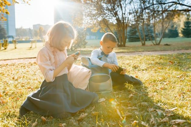 学校の子供たちの男の子と女の子は、芝生の上の秋の公園に座る