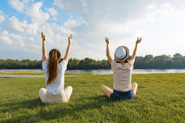 Две молодые девушки медитируют в парке у реки, вид сзади