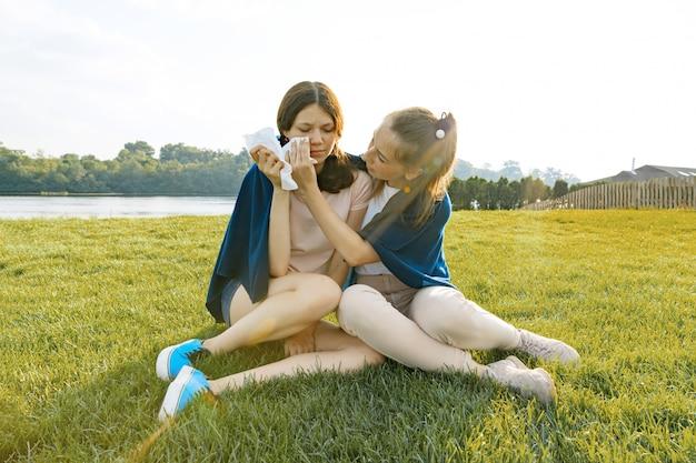 Девочка-подросток утешает своего плачущего, расстроенного, грустного друга