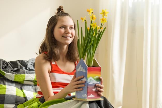 Девочка-подросток с букетом желтых весенних цветов