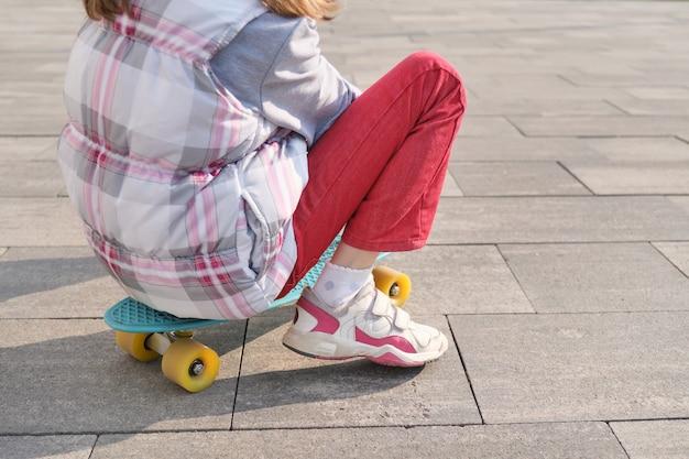 小さな女の子がスケートボードに乗る