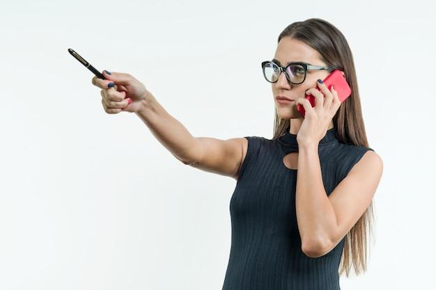 Деловая женщина с телефоном указывает с ручкой