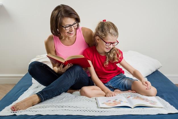 Мама и дочка читают книги дома в постели