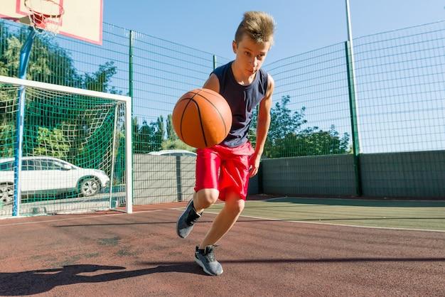 ボールで遊ぶ屋外ポートレートストリートバスケットボール選手
