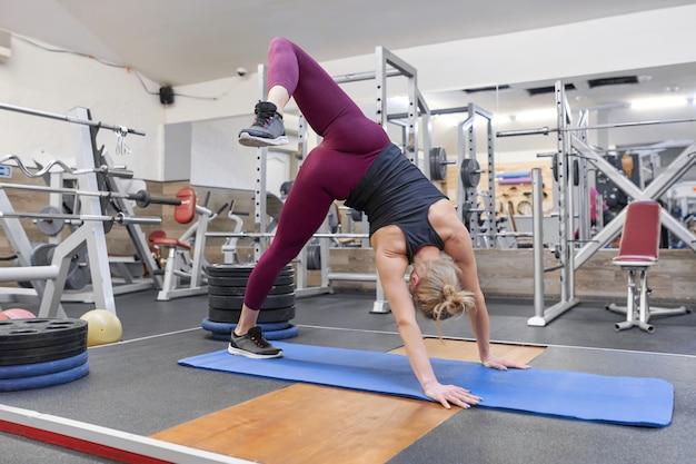 ヨガの練習をしながら体をストレッチスポーティな金髪の大人の女性