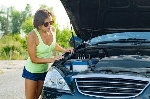 Разочарованный водитель женщина стоит возле разбитой машины на проселочной дороге