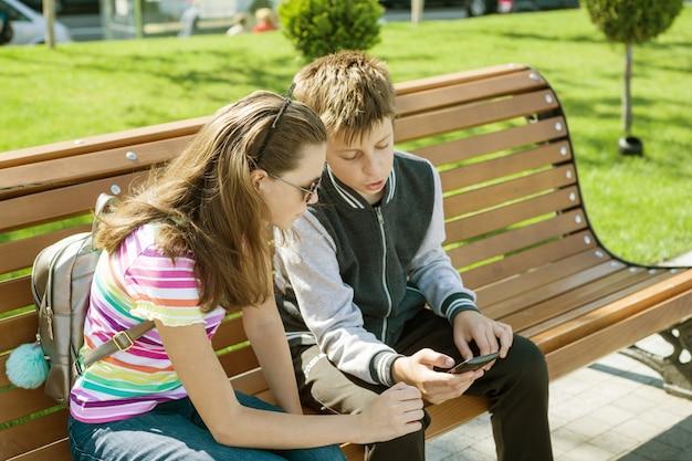 男の子と女の子のティーンエイジャーは、読み取り、スマートフォンを見て遊ぶ