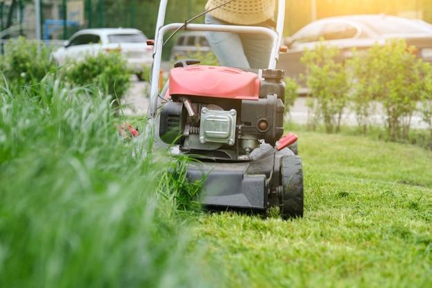 Газонокосилка косит зеленую траву, садовник с газонокосилкой работает
