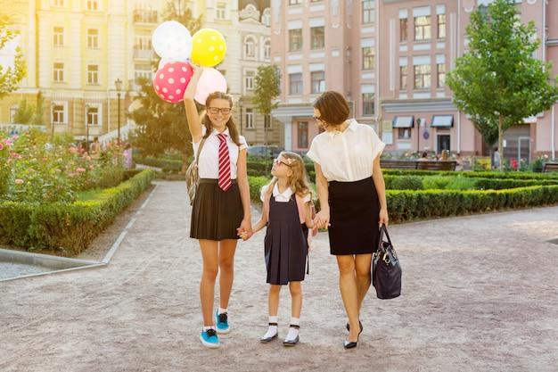Мама и дети держатся за руки, идут в школу.