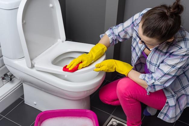 Женщина убирает в ванной. мыть туалет